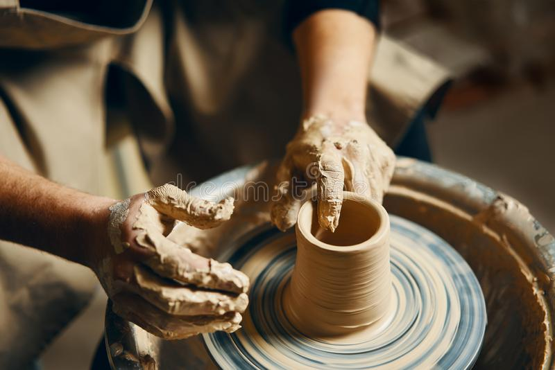 Potter modeling ceramic pot from clay on a potter`s wheel. Workshop, art concept stock photos