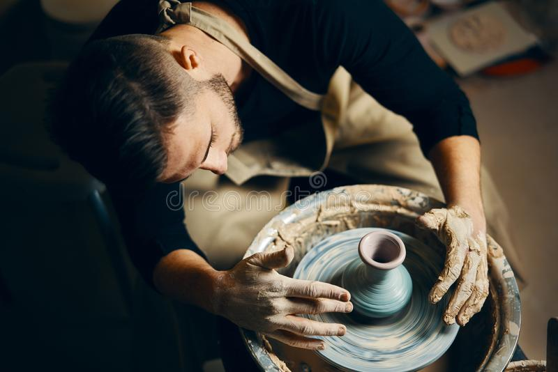 Potter modeling ceramic pot from clay on a potter`s wheel. Workshop, art concept stock image