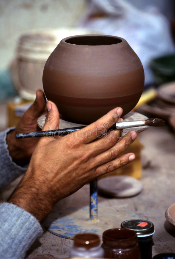 Potter- Peru. Potter beginning to apply the slip (paint) onto clay pot in workshop in the Incan village of Ollantaytambo (Sacred Valley), Peru