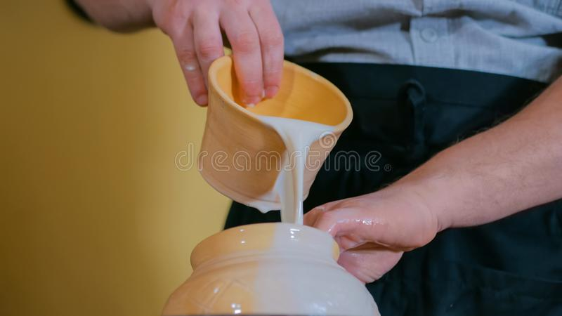 Potter preparing ceramic wares for burning. Professional male potter preparing ceramic wares for burning in pottery kiln with milk - old russian pottery royalty free stock image