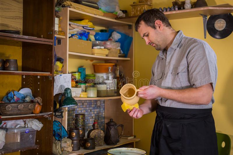 Potter preparing ceramic wares for burning. Professional male potter preparing ceramic wares for burning in pottery kiln with milk - old russian pottery stock image