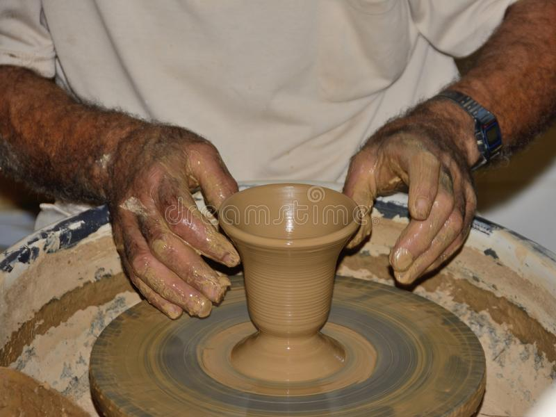Potter`s craft. Hands of the potter make a vase on a potter`s wheel, close up.  royalty free stock photos