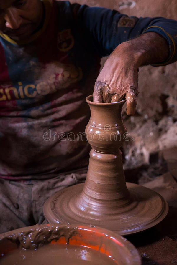 The potter`s hand shapes the clay pitcherlying on the spinning potter`s wheel stock photography