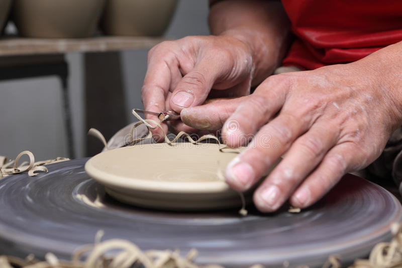 Potter's hands finishing clay plate. Potter's hands finishing a clay plate with a scraping tool on a turning wheel with a carving tool in an Asian Philippines royalty free stock photo