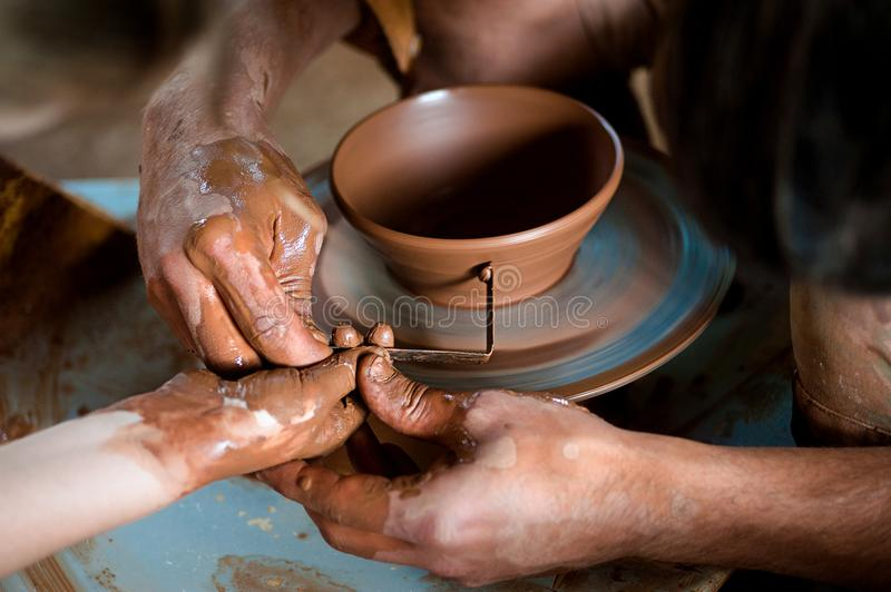 Potter`s hands guiding child`s hands to help him to work with the pottery wheel. Handcrafted on a potter`s wheel,Hands make clay from various items for home and stock photo