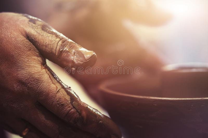 Potter`s hands while working at potter`s wheel. Sunny background stock images