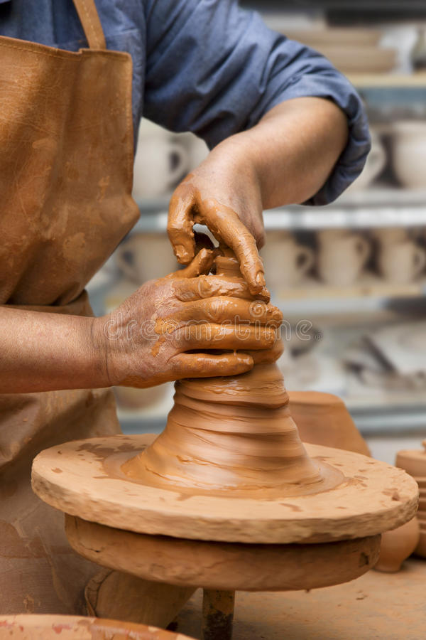 Potter's wheel. Person creating an earthen jar on the circle. Vertical royalty free stock images