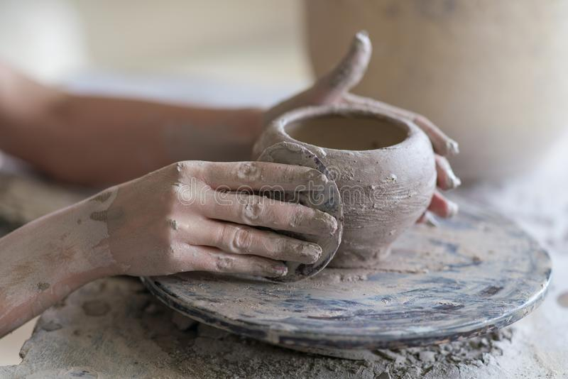 potter sculpts a vase on a potter's wheel stock images