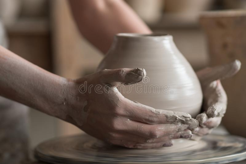 Potter sculpts a vase on a potter's wheel. The potter works in the workshop. Hands and a potter's wheel close-up stock image