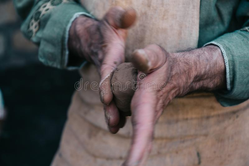 Potter works with clay, craftsman hands close up, kneads and moistens clay royalty free stock photos