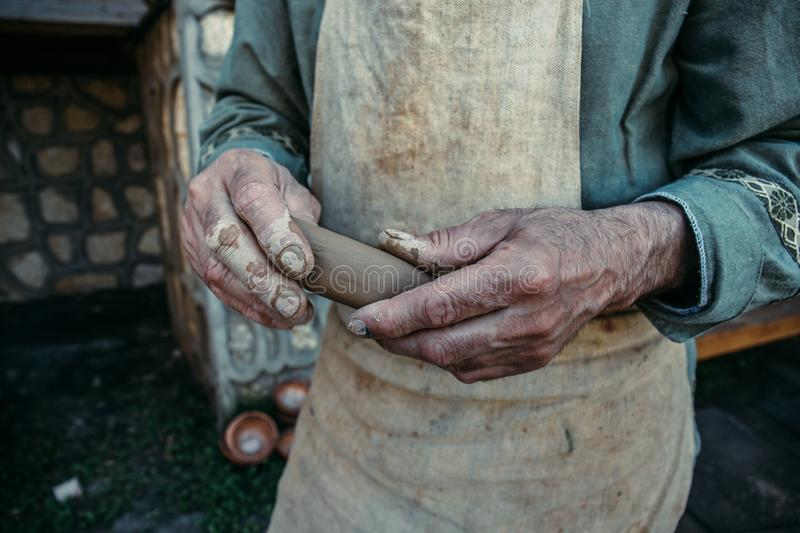 Potter works with clay, craftsman hands close up, kneads and moistens clay stock photo