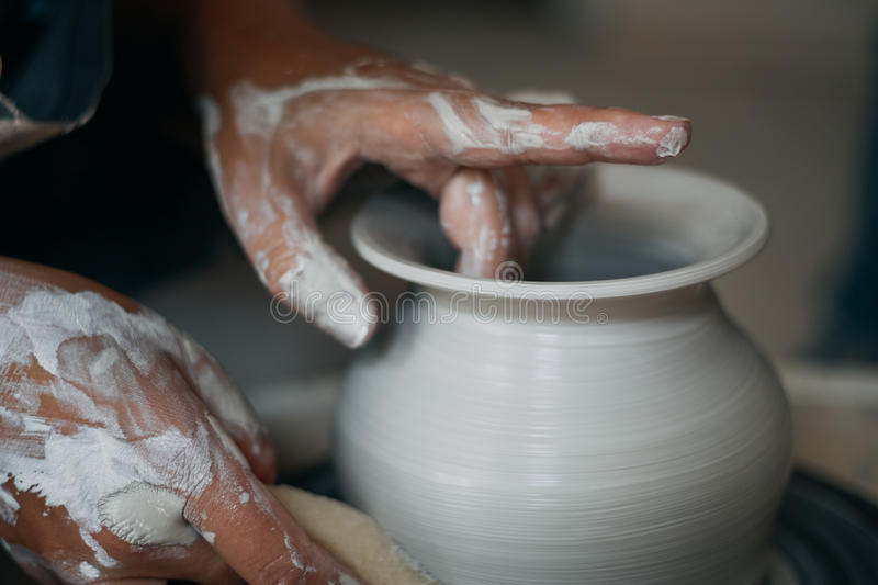 Potter works at pottery wheel, dirty woman hands stock photos
