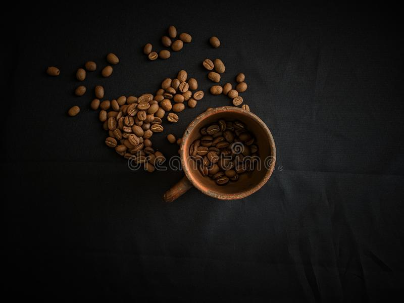 A pottery cup and coffee beans on black backdrop background stock photo