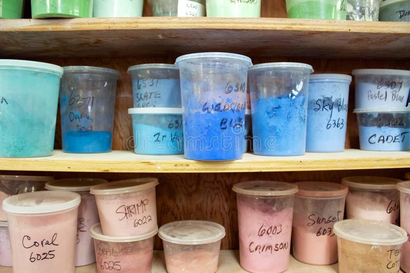 Pottery glaze in different colours in plastic containers on shelves stock image