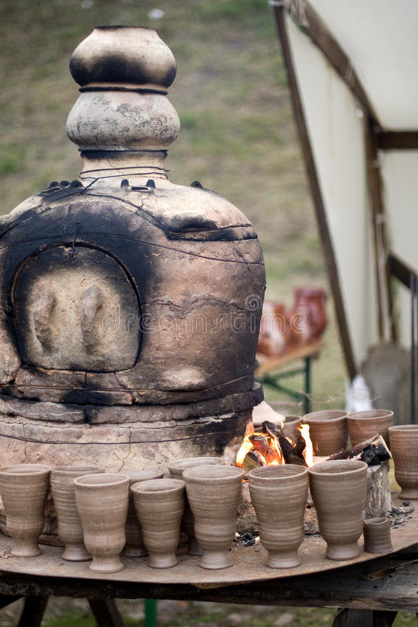 Pottery kiln. Old pottery kiln and clay mugs stock image