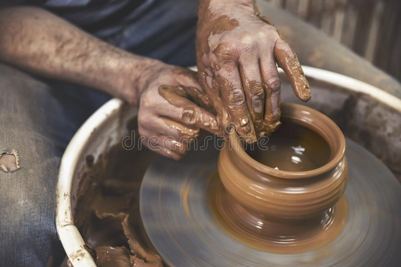 Pottery. The master at the potter`s wheel, produces a vessel of clay stock image