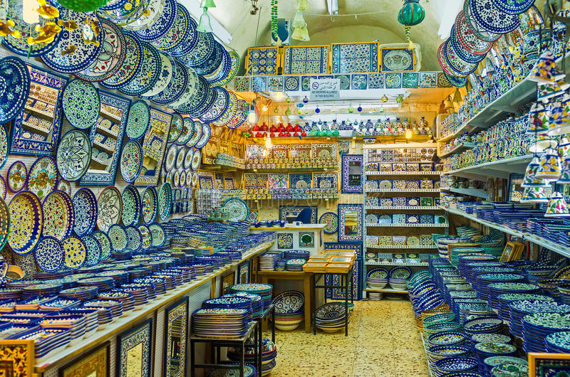 The pottery shop. JERUSALEM - FEBRUARY 15, 2016: The pottery shop in Souk El Bazaar with colorful plates and ceramic tiles, decorated with traditional arabic royalty free stock photo