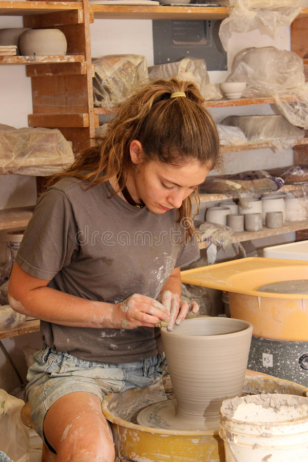 In the Pottery Studio. A teen girl working in a pottery studio throwing a pot