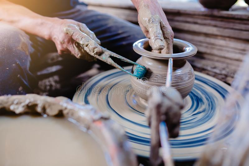 Pottery, workshop, ceramics art concept - closeup on male hands sculpt new utensil with a tools and water royalty free stock images