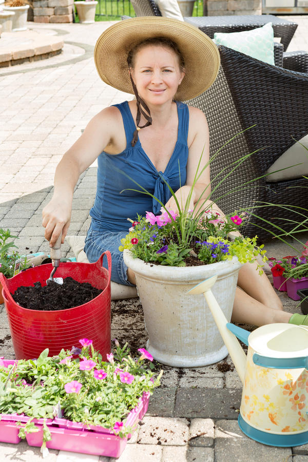 Potting de sorriso do jardineiro da senhora acima das flores da mola foto de stock royalty free
