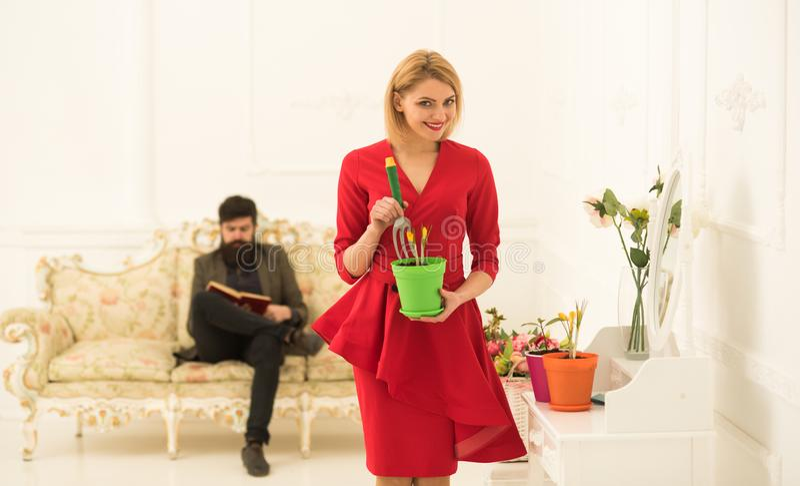 Pottingkonzept Frauenpflugblume im Pottingboden während Mannlesebuch auf Sofa Pottingmischung Potting oder lizenzfreies stockbild