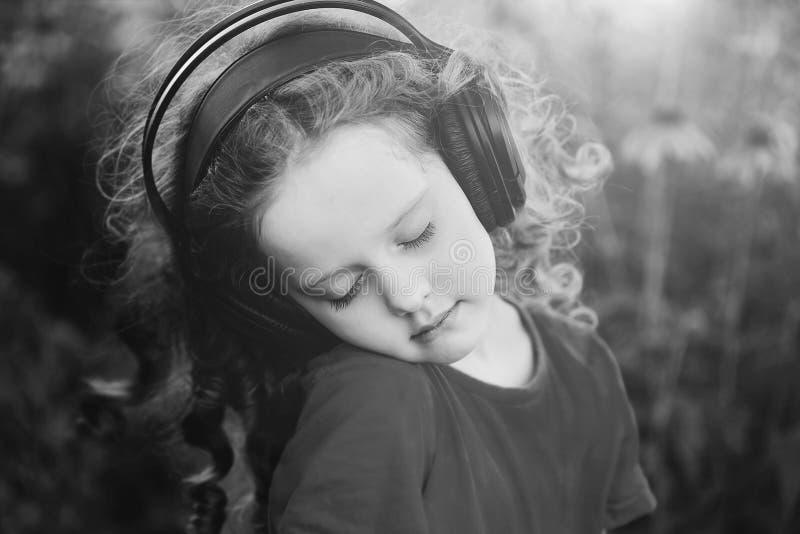 Pottrait blanco y negro una niña que escucha la música fotos de archivo