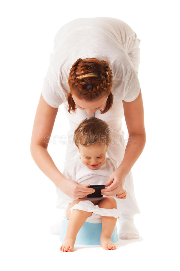 Potty training. Mother performs potty training with her son using smartphone stock images