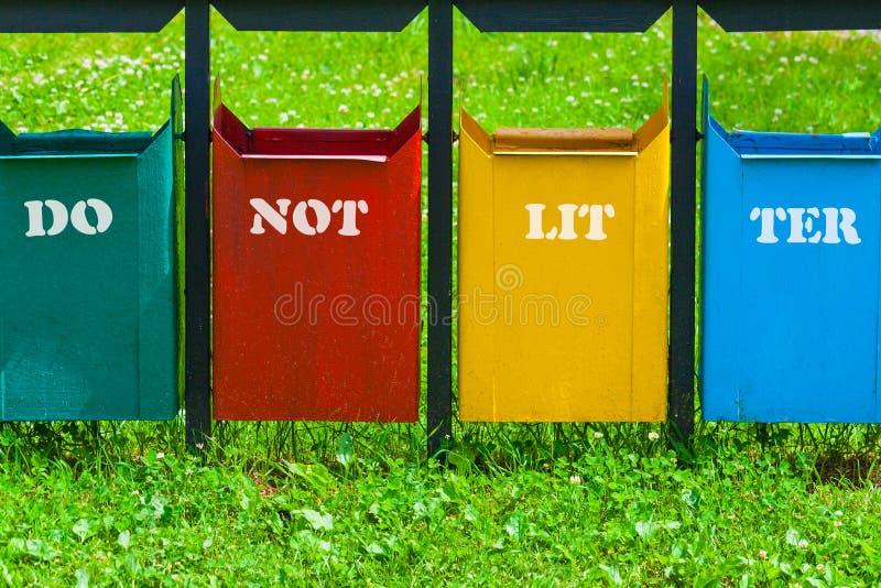 Poubelle de quatre couleurs en parc avec l'inscription images libres de droits