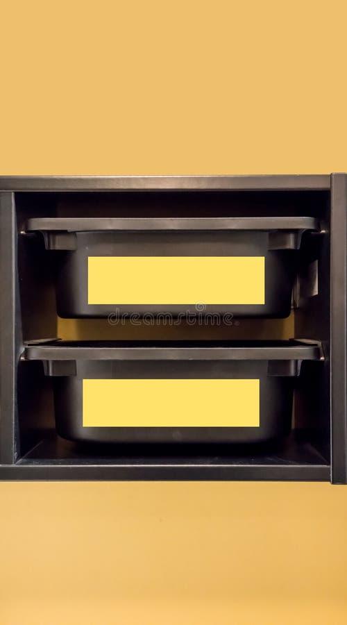 Poubelle de stockage en plastique noire avec le label jaune pour l'organisateur de pièce photos libres de droits