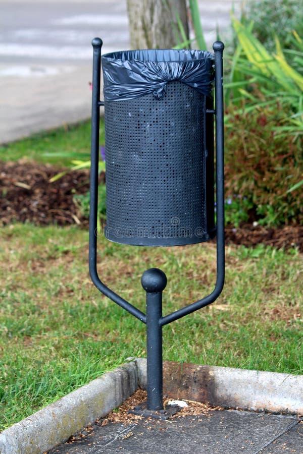 Poubelle noire en métal montée sur l'appui de forme de v avec le nouveau sac de déchets en plastique placé sur le bord du trottoi photo stock