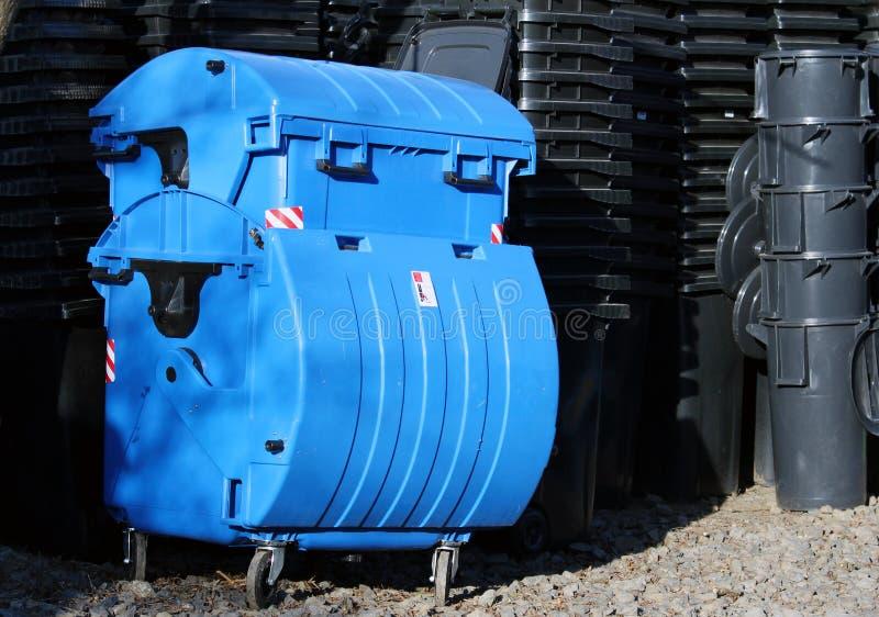 Poubelles de poussière bleues et noires de déchets municipaux image stock