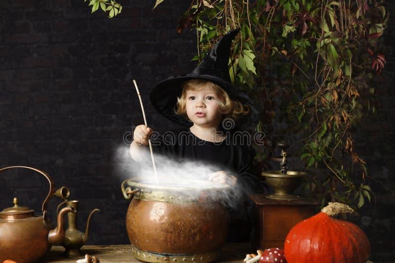 Pouca bruxa do Dia das Bruxas com caldeirão, fotos de stock