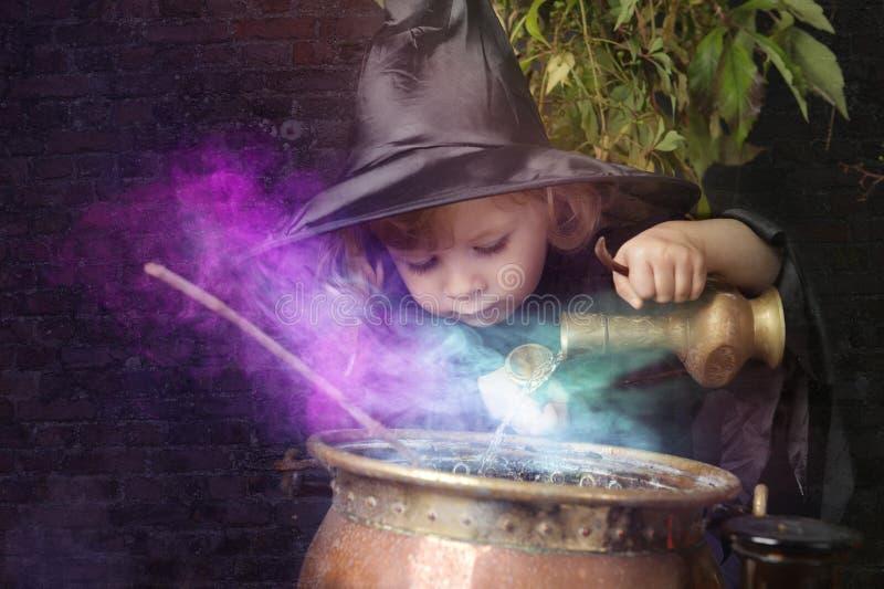 Pouca bruxa do Dia das Bruxas com caldeirão, imagem de stock royalty free