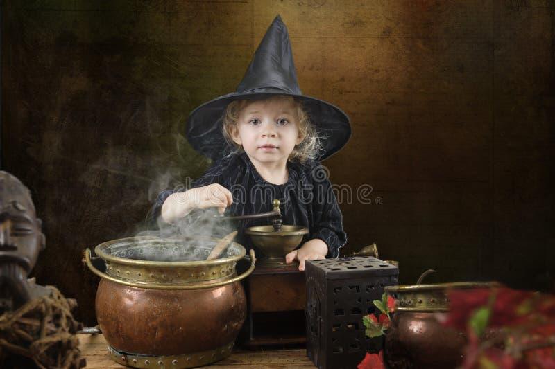 Pouca bruxa do Dia das Bruxas com caldeirão fotografia de stock
