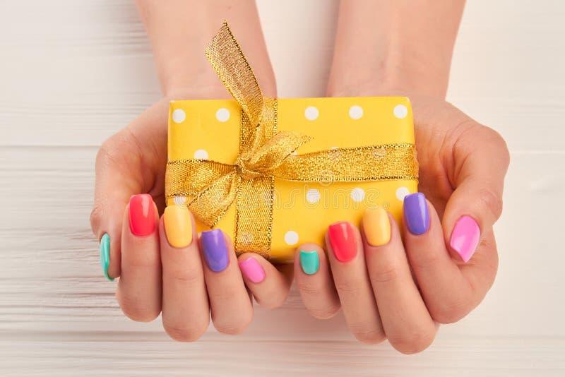 Pouca caixa de presente nas mãos manicured fêmea imagens de stock