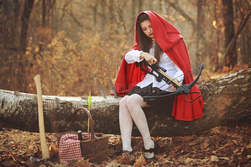 Pouca capa de equitação vermelha com uma besta fotos de stock