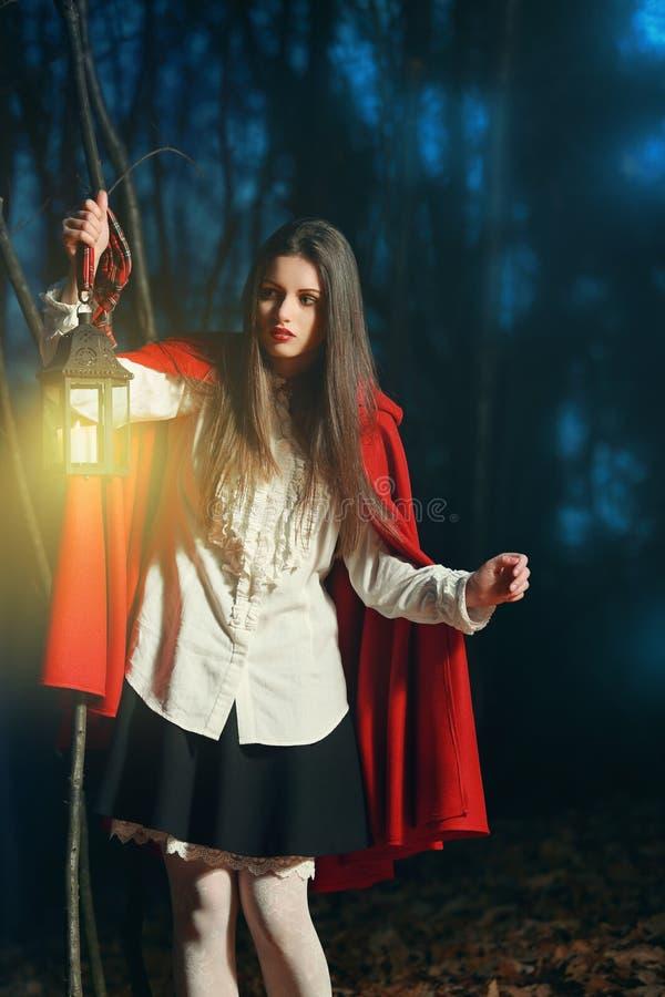 Pouca capa de equitação vermelha na floresta escura com uma lanterna imagens de stock royalty free