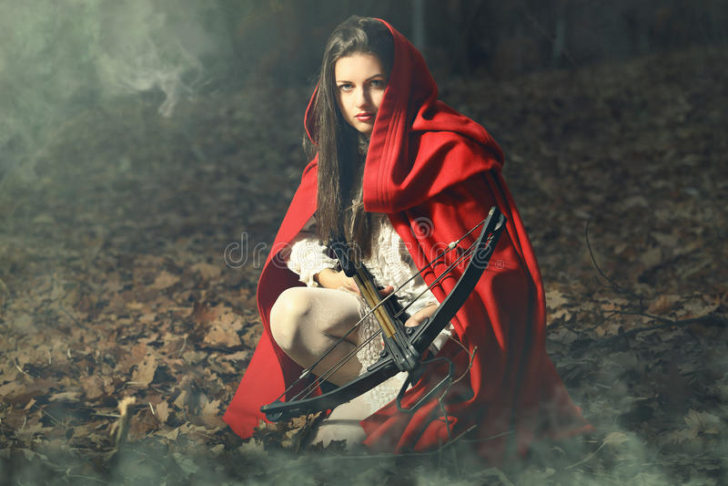 Pouca capa de equitação vermelha que espera a rapina imagens de stock