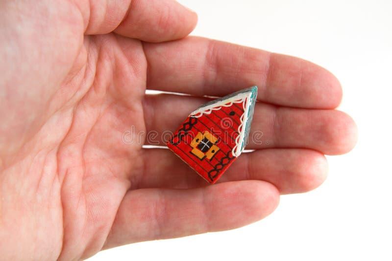 Pouca casa vermelha em uma mão fotografia de stock royalty free