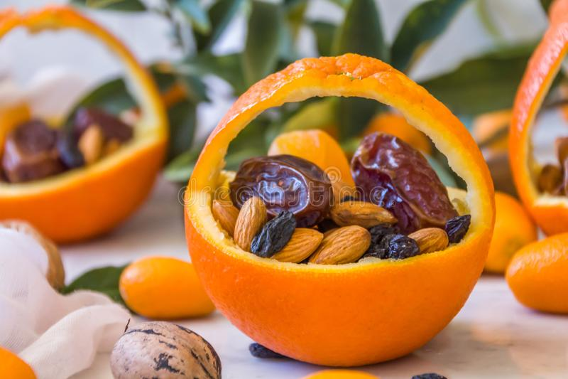 Pouca cesta fez da laranja fresca enchida com os frutos secos; amêndoas, datas, passas e porcas fotos de stock royalty free