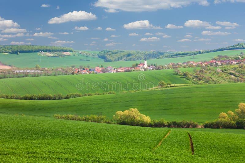 Pouca cidade nos montes verdes, no céu azul, nas casas do smalll e no natu imagens de stock