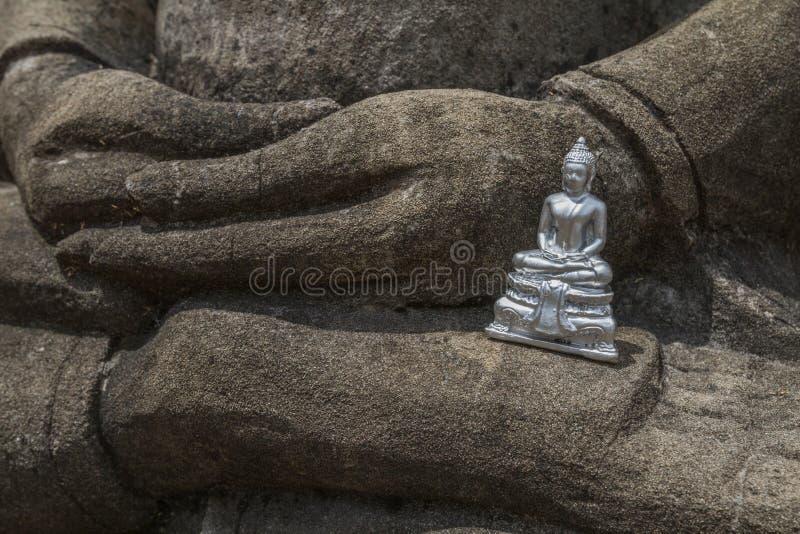 Pouca estatueta de prata de buddha em uma estátua de pedra cinzenta grande de buddha fotos de stock