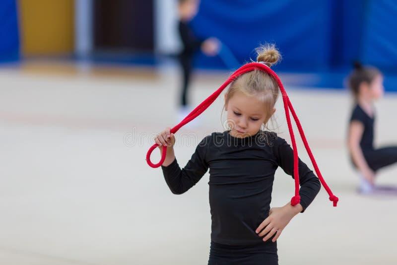 Pouca ginasta est? guardando a corda sobre sua cabe?a ao exercitar foto de stock royalty free