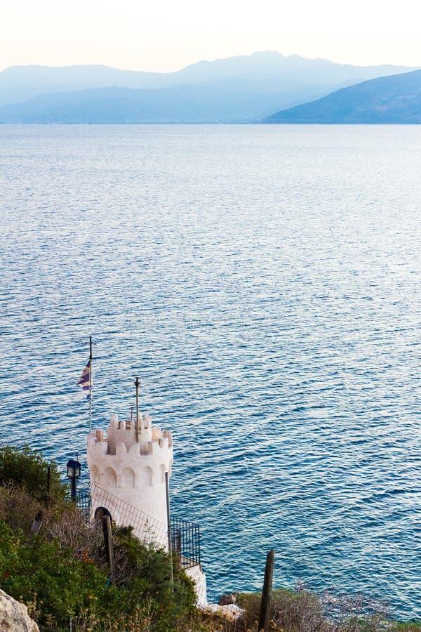 Pouca igreja com a bandeira grega no litoral rochoso imagens de stock