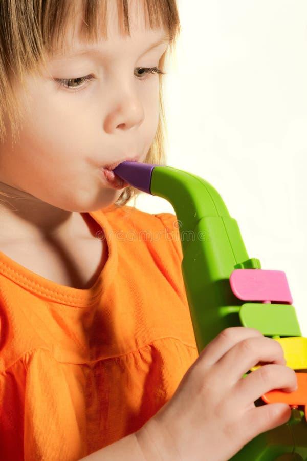 Pouca menina da beleza com saxofone do brinquedo imagens de stock royalty free