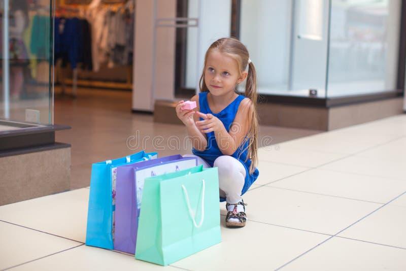 Pouca menina da fôrma senta-se perto dos pacotes em um grande imagens de stock