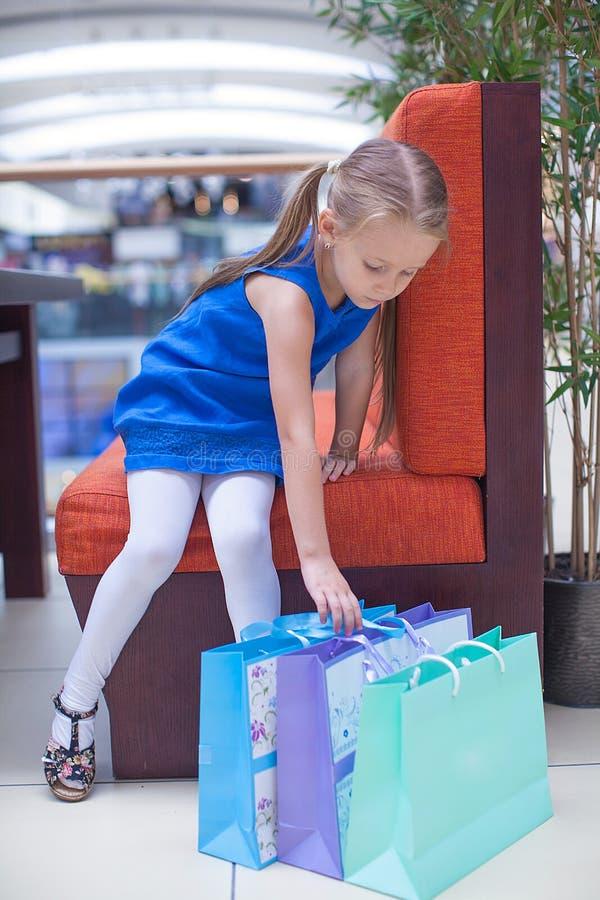 Pouca menina da forma senta-se perto dos pacotes em um grande fotos de stock royalty free