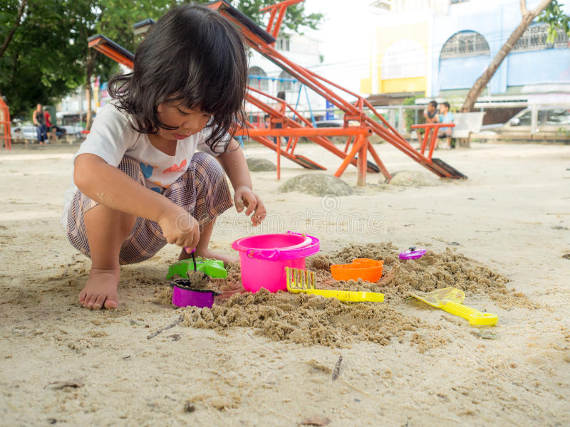 Pouca menina de Ásia que senta-se na caixa de areia e que joga a cubeta e a da pá do brinquedo do whit estava escavando na cubeta imagens de stock royalty free