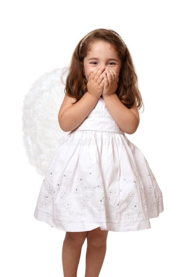 Pouca menina do anjo com as mãos que cobrem sua boca fotos de stock royalty free