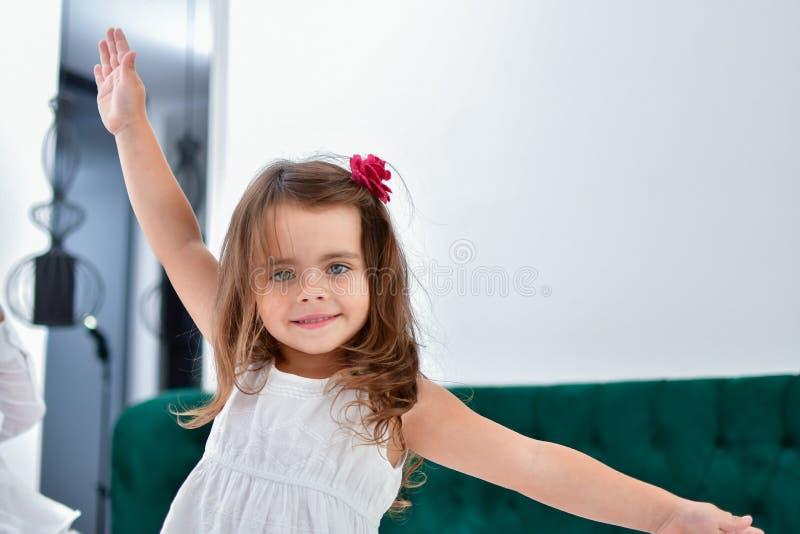 Pouca menina dos sorrisos com uma flor em seu cabelo imagens de stock